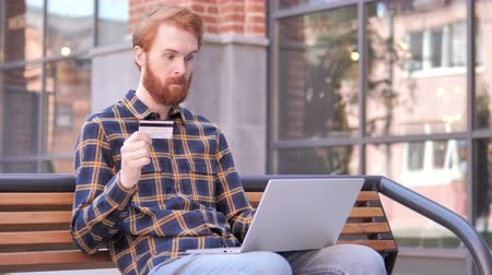 roodharige : Online Shopping by Redhead Beard Young Man Sitting on Bench