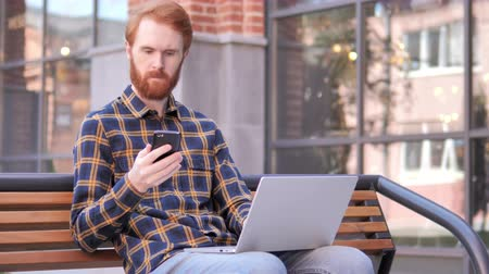 vöröshajú : Redhead Beard Young Man Using Smartphone and Laptop, Sitting on Bench