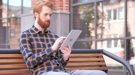 roodharige : Redhead Beard Man Using Tablet While Sitting On Bench Stockvideo