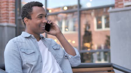 discar : African Man Talking on Phone Sitting Outdoor Stock Footage