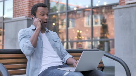 discar : African Man Talking on Phone, Sitting on Bench Stock Footage