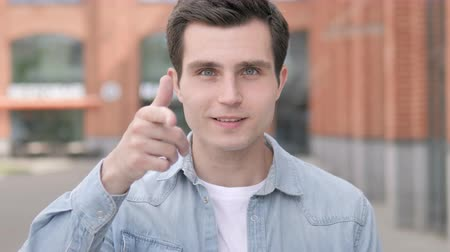 convidar : Young Man Pointing with Finger Outdoor