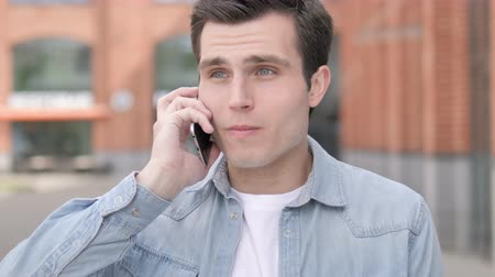 discar : Angry Young Man Talking on Phone Stock Footage