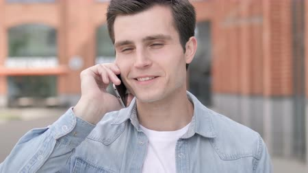 discar : Outdoor Young Man Talking on Phone Stock Footage