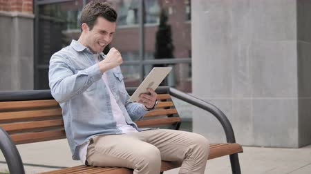 tab : Casual Young Man Sitting Outdoor