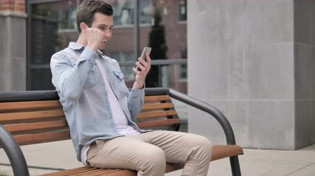 görgetés : Outdoor Young Man Excited for Success on Smartphone