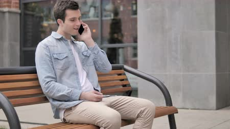 ławka : Casual Young Man Talking on Phone Sitting Outdoor