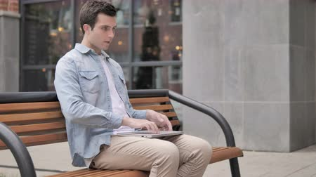 urlop : Young Man Closing Laptop and Leaving Bench