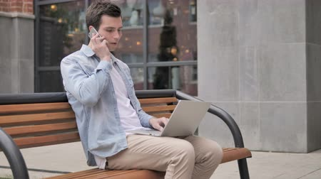 discar : Young Man Talking on Phone while Sitting on Bench Stock Footage