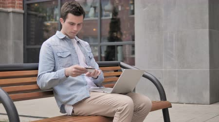 sem problemas : Online Shopping Failure for Young Man Sitting on Bench