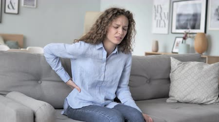 primeiro socorro : Curly Hair Woman with Spinal Back Pain Sitting on Couch Stock Footage