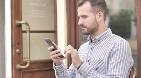 prohlížeč : Young Man Using Smartphone while Sitting Outdoor