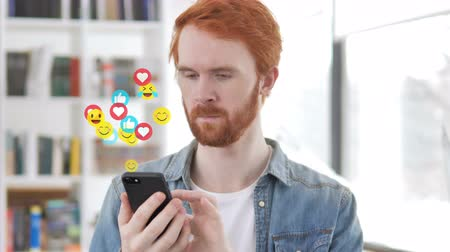 görgetés : Redhead Beard Designer Using Smartphone, Flying Emojis, Smileys and Likes Stock mozgókép