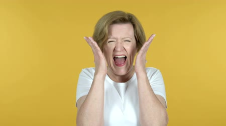 逆境 : Screaming Angry Old Woman Isolated on Yellow Background 動画素材