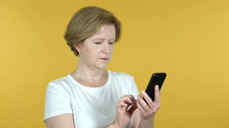 e mail address : Old Woman Browsing Smartphone Isolated on Yellow Background