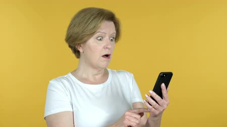 e mail address : Old Woman Reacting and Using Smartphone Isolated on Yellow Background Stock Footage