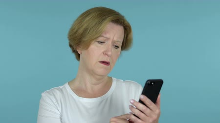 e mail address : Old Woman Reacting To herself and Smart Phone Isolated on Blue Background Stock Footage