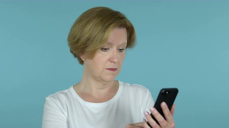 e mail address : Amazed Old Woman Excited while Using Smartphone Isolated on Blue Background
