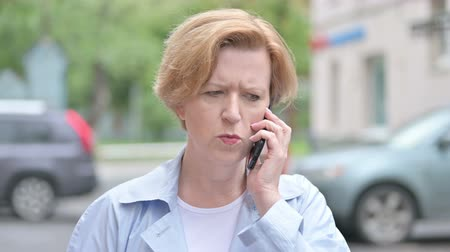 adversidade : Angry Old Woman Talking on Phone, Outdoor Stock Footage