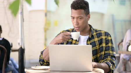 терраса : Young African Man Drinking Coffee Стоковые видеозаписи