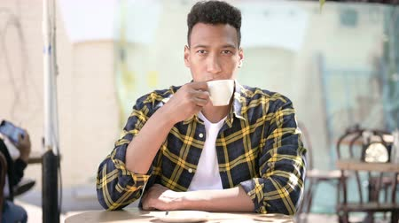 afro amerikan : Relaxing Young African Man Drinking Coffee, Outdoor Cafe Stok Video