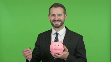 копилку : cheerful Businessman putting Money in Piggy Bank against Chroma Key Стоковые видеозаписи