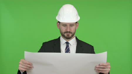 gezichtsuitdrukking : Ambitieuze Engineer Reading Construction Blueprint tegen Chroma Key