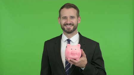 копилку : Young Businessman holding Piggy Bank against Chroma Key