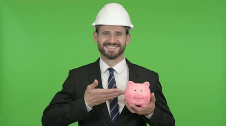 копилку : Cheerful Engineer holding Piggy Bank against Chroma Key Стоковые видеозаписи