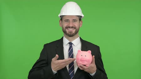 возвращение : Cheerful Engineer pointing at Piggy Bank against Chroma Key