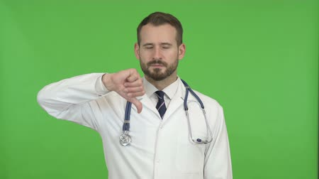 разочарование : Young Doctor Showing Thumbs Down against Chroma Key