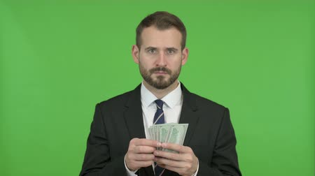 invite : Young Businessman Counting and Offering Money against Chroma Key