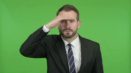 merging : Ambitious Businessman trying to Look far off against Chroma Key