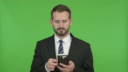 összeg : Young Businessman taking out Money from Wallet against Chroma Key