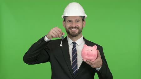 currency trading : Happy Engineer holding Piggy Bank with House key against Chroma Key
