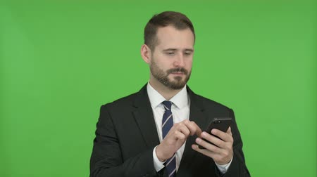 gritar : Cheerful Businessman Scrolling his Cellphone against Chroma Key Vídeos