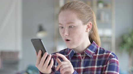 поражение : Young Woman Using Smartphone With Shocked Expression