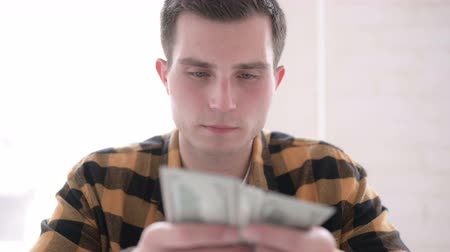 one man only : Young Man Counting Dollar Paper Currency