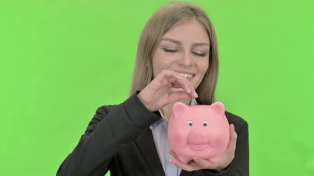 копилку : Businesswoman Inserting Coin in Piggy Bank against Chroma Key