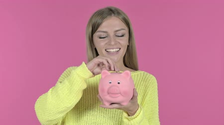 копилку : Ambitious Young Girl Inserting Coin in Piggy Bank, Pink Background