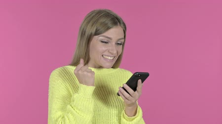 görgetés : Excited Girl Cheering Success while Using Smartphone, Pink Background