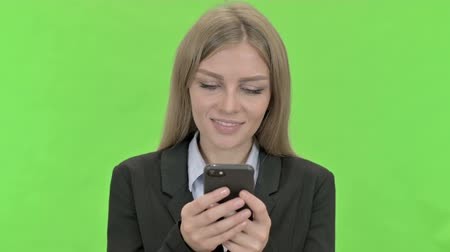 a böngésző : Young Businesswoman Using Smartphone against Chroma Key Stock mozgókép