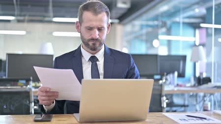 introspection : Young Businessman reading Documents on Office Desk