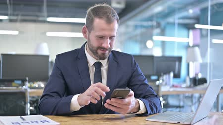 adults only : Successful Young Businessman Celebrating on Smartphone