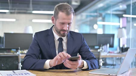 introspection : Young Businessman Celebrating on Smartphone with Fist Stock Footage
