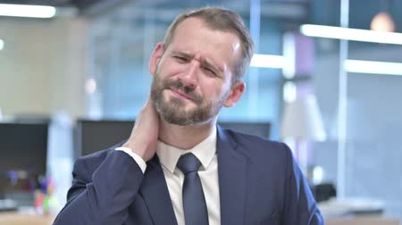 массаж : Portrait of Tired Businessman having Neck Pain in Office