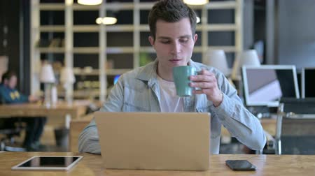 káva : Hardworking Young Designer Drinking Coffee in Modern Office