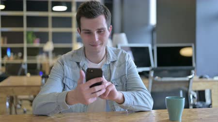 prohlížeč : Attractive Young Designer using Smartphone in Modern Office