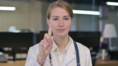 medical student : Portrait of Attractive Young Female Doctor saying No by Finger
