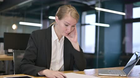introspection : Young Businesswoman Reacting to Loss on Documents in Office